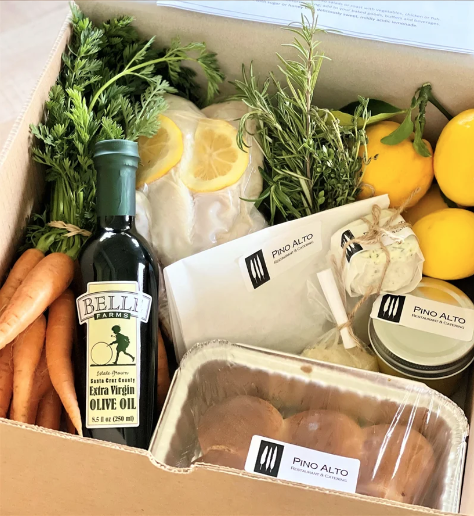 culinary market box filled with carrots, olive oil, bread, lemons