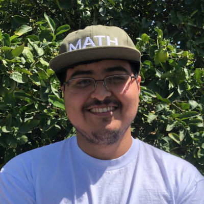 Jesse smiling. He has on a white shirt and a sage green hat that says Math